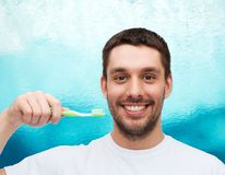 Smiling young man with toothbrush Stock Photography