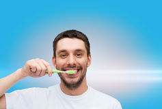 Smiling young man with toothbrush Stock Photos