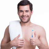 Smiling young man with a toothbrush. Royalty Free Stock Images