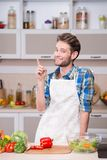 Smiling young man trying to cook dinner in kitchen Stock Photo