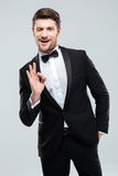 Smiling young man in tuxedo with bowtie showing ok sign Royalty Free Stock Photo