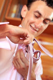 Smiling young man tying a tie Stock Image