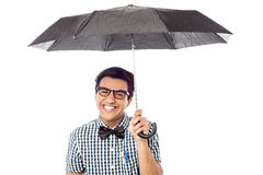 Smiling young man with an umbrella. Cheerful man with opened umbrella, isolated on white Stock Image