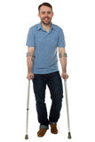 Smiling young man using crutches Royalty Free Stock Images