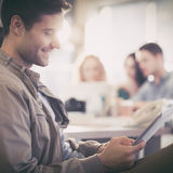 Smiling young man using digital tablet. Smiling young men using digital tablet in the office royalty free stock photo