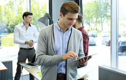 Smiling young man using digital tablet in the office. Stock Photo