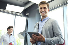 Smiling young man using digital tablet in the office. Stock Photography