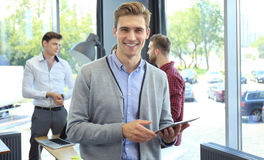 Smiling young man using digital tablet in the office. Royalty Free Stock Photo