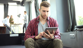Smiling young man using digital tablet in the office. Royalty Free Stock Photos