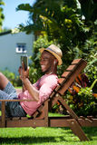 Smiling young man using digital tablet. Side portrait of smiling young man sitting on chair outdoors and using digital tablet Royalty Free Stock Photo