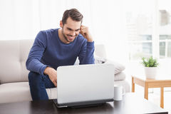 Smiling young man using his laptop Stock Photography