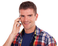 Smiling young man using his phone Royalty Free Stock Photo