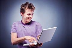 Smiling young man using laptop. Studio shot of a young man using laptop Royalty Free Stock Image
