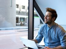 Smiling young man using laptop stock image