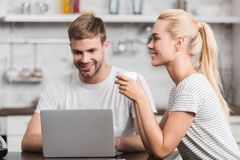 Smiling young man using laptop while happy girlfriend. Drinking coffee stock image