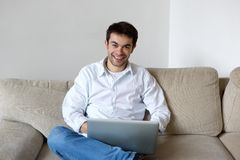 Smiling young man using laptop at home Royalty Free Stock Image