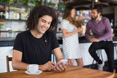 Smiling young man using mobile phone while sitting in restaurant Royalty Free Stock Photos