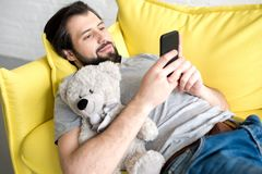 Smiling young man using smartphone while lying on sofa and hugging. Teddy bear royalty free stock photo
