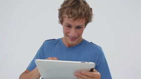 Smiling young man using a tablet computer Royalty Free Stock Images