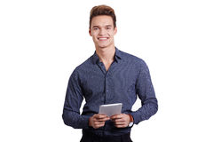 Smiling young man using tablet computer against a white background Royalty Free Stock Photography