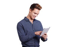 Smiling young man using tablet computer against a white background Stock Photos
