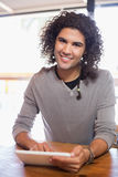 Smiling young man using tablet pc in restaurant Royalty Free Stock Photos