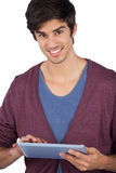 Smiling young man using tablet pc Royalty Free Stock Photos