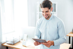 Smiling young man using tablet at workplace. Smiling young man standing and using tablet at workplace Stock Photo