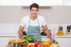 Smiling young man with vegetables standing in kitchen Stock Images