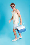 Smiling young man walking and holding cooler bag stock photography