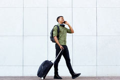 Smiling young man walking with luggage and mobile phone. Full length portrait of smiling young man walking with luggage and mobile phone Royalty Free Stock Photos
