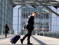 Smiling young man walking with luggage at station Royalty Free Stock Photos