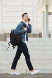 Smiling young man walking outside with bag and cellphone. Full length portrait of smiling young man walking outside with bag and cellphone Stock Image