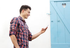 Smiling young man walking outside with mobile phone Stock Images