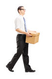 Smiling young man walking with a paper box in his hands Stock Photos