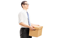Smiling young man walking with a paper box in his hands Royalty Free Stock Photos