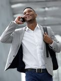 Smiling young man walking and talking on mobile phone Stock Photo