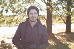 Smiling young man in warm clothing in forest Stock Images