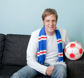 Smiling young man watching football at home Stock Photo