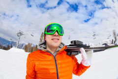 Smiling young man wearing mask holds ski in winter Stock Image