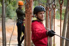 Smiling young man wearing safety helmet crossing zip line cable in background woman waiting for him. In the forest Royalty Free Stock Image