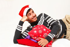 Smiling young man wearing a Santa Claus hat with pillows Royalty Free Stock Photo