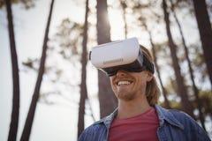 Smiling young man wearing virtual reality simulator Stock Photos