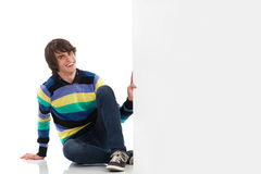 Smiling young man with a white placard. Royalty Free Stock Image