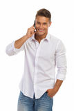 Smiling Young Man In A White Shirt On The Phone. Handsome smiling young man in white unbuttoned shirt and jeans shorts standing relaxed with hand in pocket and Royalty Free Stock Images