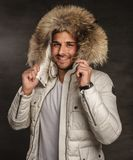 A man in a coat. Smiling young man in winter warm coat with fur hood Royalty Free Stock Photography