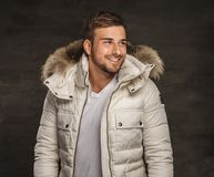 A man in a coat. Smiling young man in winter warm coat with fur hood Royalty Free Stock Images