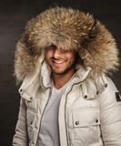 A man in a coat. Smiling young man in winter warm coat with fur hood Stock Images