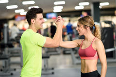 Smiling young man and woman doing high five in gym Stock Photos