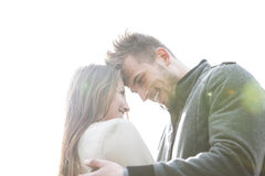 Smiling young man and woman embracing against clear sky Stock Images